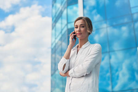 Businesswoman successful woman business person standing outdoor corporate building exterior cell phone Pensive elegance cute caucasian professional business woman middle age dreaming with mobile phone