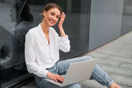 Businesswoman successful woman business person outdoor corporate building exterior with laptop Pensive elegance cute caucasian professional business woman middle age ecommerce deal Online banking 免版税图像