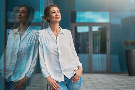 Businesswoman successful woman business person standing outdoor corporate building exterior Pensive elegance cute caucasian confidence professional business woman middle age dreaming Bank worker