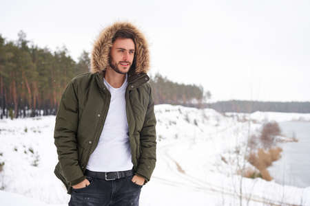 Handsome bearded young caucasian man standing outdoors fur hood in winter season forest. Attractive stylish european guy walking snowy christmas woodland Season holiday leisure 版權商用圖片
