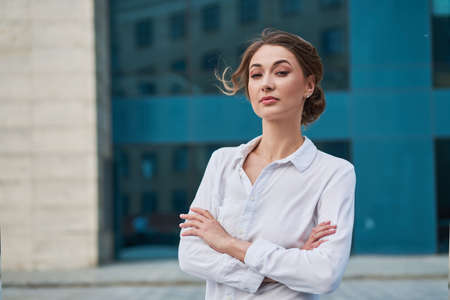 Businesswoman successful woman business person standing arms crossed outdoor corporate building exterior Pensive elegance caucasian confidence professional business woman middle age female leader