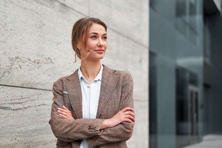 Businesswoman successful woman business person standing arms crossed outdoor corporate building exterior Smile happy caucasian confidence professional business woman middle age female entrepreneur