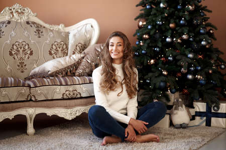 Christmas. Woman dressed white sweater and jeans sitting on the floor near christmas tree with present box Caucasian female middle age relaxing winter holiday at home interior New year mood 版權商用圖片