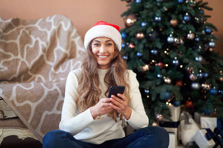 Christmas Woaman dressed white sweater Santa hat sitting on floor near christmas tree Caucasian female relaxing winter holiday using smartphone Online shopping sale season