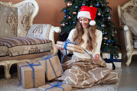 Christmas Woman white sweater Santa hat sitting floor near christmas tree wrapped herself blanket. Caucasian female middle age relaxing winter holiday at home interior with plaid open gift box