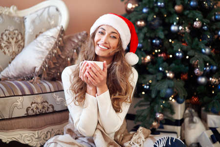 Christmas Woman dressed white sweater Santa hat sitting on floor near christmas tree wrapped herself blanket Caucasian female relaxing winter holiday at home interior with plaid drink hot coffee