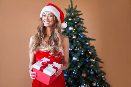 Christmas Woman red dress costume Santa hat standing near christmas tree. Caucasian female middle age relaxing winter holiday at home interior open gift box