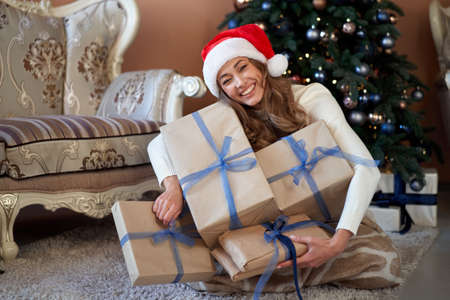 Christmas Woman white sweater Santa hat sitting floor near christmas tree wrapped herself blanket. Caucasian female winter holiday home interior with plaid open gift box greed many gifts 版權商用圖片