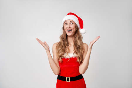 Woman christmas Santa Hat white studio background Beautiful caucasian female curly hair portrait Happy person positive emotion Holiday concept threw hands up Shows great. 版權商用圖片