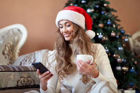 Christmas Woman dressed white sweater Santa hat sitting on floor near christmas tree wrapped herself blanket Caucasian female relaxing winter holiday plaid drink hot coffee using smartphone
