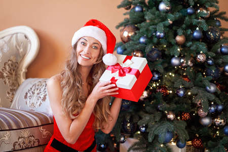 Christmas Woman red dress costume Santa hat sitting floor near christmas tree. Caucasian female middle age relaxing winter holiday at home interior open gift box
