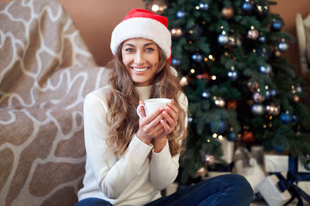 Christmas Woaman dressed white sweater Santa hat sitting floor near christmas tree wrapped herself blanket Caucasian female relaxing winter holiday at home interior with plaid drink hot morning coffee 版權商用圖片