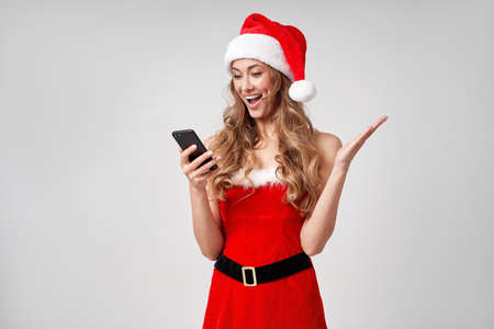 Woman christmas Santa Hat white studio background with smartphone in hand Beautiful caucasian female curly hair portrait. Surprised person positive emotion Holiday concept with copy space Teeth smiling