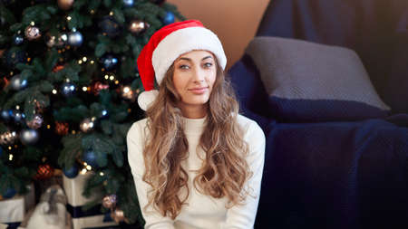 Christmas. Woman dressed white sweater jeans santa hat sitting on the floor near christmas tree with present box Caucasian female middle age relaxing winter holiday at home interior New year mood