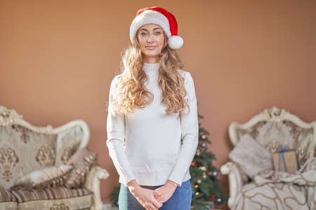 Christmas. Woman dressed white sweater Santa hat and jeans standing near christmas tree Caucasian female middle age relaxing winter holiday at home interior New year mood 版權商用圖片