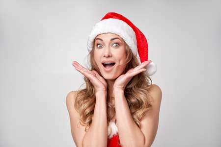 Woman christmas Santa Hat white studio background Beautiful caucasian female curly hair portrait Happy person positive emotion Holiday concept Close up face portrait with hand