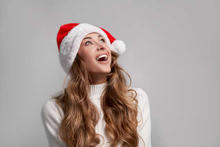 Woman christmas Santa Hat sweater white studio background Beautiful caucasian female curly hair portrait Happy person positive emotion Holiday concept Surprised face portrait looking up open mouth WOW 版權商用圖片