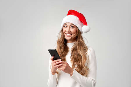 Woman christmas Santa Hat white sweater white studio background with smartphone in hand Beautiful caucasian female curly hair portrait. Happy person positive emotion Holiday concept Teeth smiling 版權商用圖片