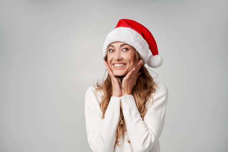 Woman christmas Sants Hat sweater white studio background Beautiful caucasian female curly hair portrait Happy person positive emotion Holiday concept Hands on face Surprised