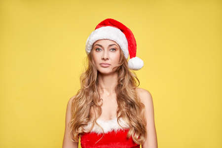 Woman christmas Santa Hat yellow studio background Beautiful caucasian female curly hair portrait Serious person sad emotion Holiday concept with copy space bad mood melancholy