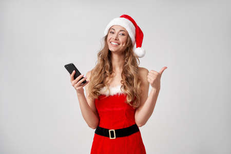 Woman christmas Santa Hat white studio background with smartphone in hand Beautiful caucasian female curly hair portrait Person positive emotion Holiday concept with copy space Teeth smiling Thumbs up 版權商用圖片