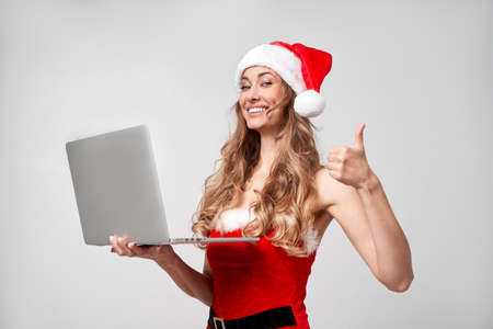 Woman christmas Santa Hat white studio background Beautiful caucasian female curly hair portrait Happy person positive emotion Holds laptop in hand Holiday concept Showing thumbs up gesture