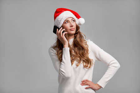 Woman christmas Santa Hat white sweater white studio background talking smartphone in hand Beautiful caucasian female curly hair portrait. Happy person positive emotion Holiday concept Teeth smiling