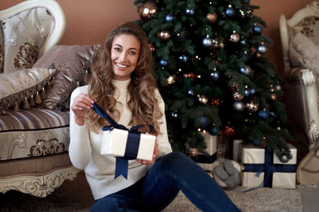 Christmas. Woman dressed white sweater and jeans sitting on the floor near christmas tree with present box Caucasian female middle age opens gifts winter holiday at home interior New year mood