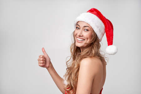 Woman christmas Santa Hat white studio background Beautiful caucasian female curly hair portrait Happy person positive emotion Holiday concept Showing Thumbs up gesture advertise some thing