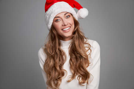 Woman christmas Santa Hat sweater white studio background Beautiful caucasian female curly hair portrait Happy person positive emotion Holiday concept Close up face portrait