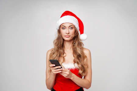 Woman christmas Santa Hat white studio background with smartphone in hand Beautiful caucasian female curly hair portrait Serious person sad emotion Holiday concept with copy space bad mood melancholy 版權商用圖片