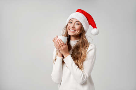 Woman christmas Santa Hat sweater white studio background Beautiful caucasian female curly hair portrait Happy person positive emotion Holiday concept Drink hot coffee white cup Cozy mood