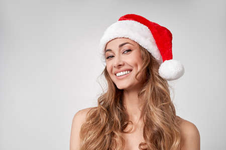 Woman christmas Santa Hat white studio background Beautiful caucasian female curly hair portrait Happy person positive emotion Holiday concept Close up face portrait 版權商用圖片