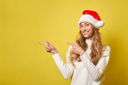 Woman christmas Santa Hat sweater yellow studio background Beautiful caucasian female curly hair portrait Happy person positive emotion Holiday concept Shows finger on side cope space for advertise