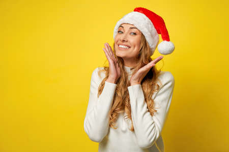 Woman christmas Santa Hat white sweater yellow studio background Beautiful caucasian female curly hair portrait Happy person positive emotion Holiday concept Hands on face Surprised