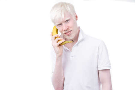Happy albino man white skin hair studio dressed t-shirt isolated white background. abnormal deviations unusual appearance abnormality Beautiful people with special appearance. use banana as a phone