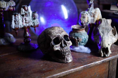 Halloween background Shelves with alchemy tools Skull spiderweb bottle with poison candles Witcher workspace Scarry room Фото со стока