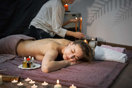Relax and enjoy spa salon getting massage professional masseur Woman lying naked back relax on floor blanket Body care Hands treatment Acupressure trigger points Prevention back muscles pain