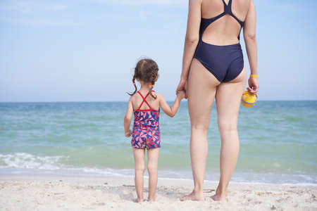 Mother daughter beach together rear view Unrecognizable caucasian woman little girl swimwear standing seaside back Family with one child. Family Vacation Summertime