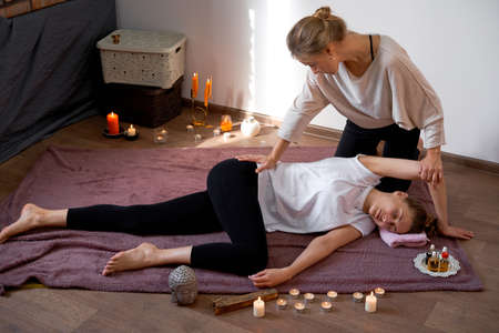 Relax and enjoy in spa salon getting thai massage by professional masseur Woman lying floor blanket Body care Hands treatment Acupressure trigger points Prevention muscles pain stretching flexibility