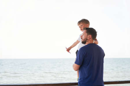 Father son together outside showing finger sea horizon back Man child spending time vacation enjoying summer Family with one child. Caucasian person beach