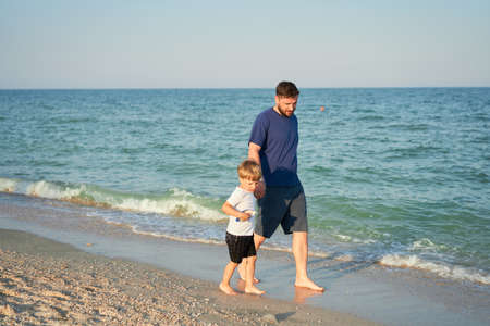 Dad holds son hand. Father Child spending time together sea vacation Young man little boy walking beach Fathers day. Family with one child. Happy childhood with daddy. Full lenght