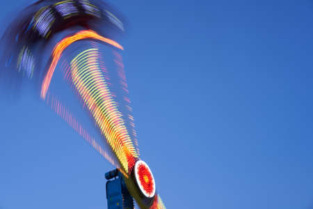 Amusement park blurred effect. Abstract illuminated background Spinning defocused carnival carousel long exposure shooting 스톡 콘텐츠