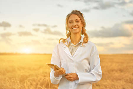 Woman farmer white coat smart farming standing farmland smiling using digital tablet Female agronomist specialist research monitoring analysis data agribusiness Caucasian worker agricultural field 스톡 콘텐츠 - 165320784