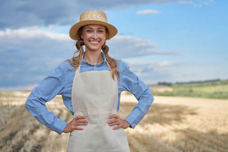 Woman farmer straw hat apron standing farmland smiling Female agronomist specialist farming agribusiness Happy positive caucasian worker agricultural field Girl hands on waist cloudy sky background