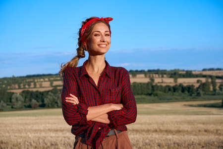 Woman farmer standing farmland smiling Female agronomist specialist farming agribusiness Happy positive caucasian worker agricultural field Pretty girl dressed red checkered shirt and bandana