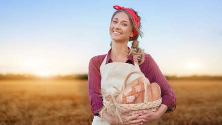 Female farmer standing wheat agricultural field Woman baker holding wicker basket bread eco product Baking small business Caucasian person dressed red checkered shirt apron organic healthy food 스톡 콘텐츠