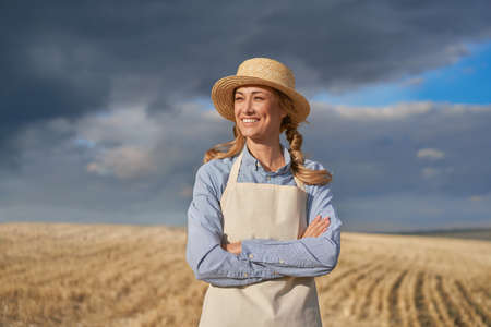 Woman farmer straw hat apron standing farmland smiling Female agronomist specialist farming agribusiness Positive caucasian worker agricultural field arms crossed cloudy sky background before rain