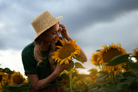 Woman agronomist standing agricultural sunflower field Caucasian female farmer straw hat Portrait agribusiness worker Businesswoman in field planning their income. Farming concept