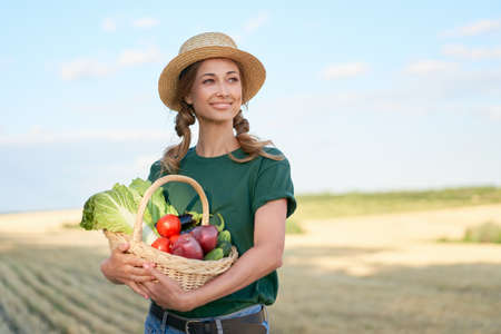 Woman farmer straw hat holding basket vegetable onion tomato salad cucumber standing farmland smiling Female agronomist specialist farming agribusiness 스톡 콘텐츠